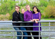 Four young multi ethnic friends together outdoors by lake Stock Photo