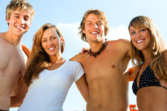 Four young people on the beach stock photo