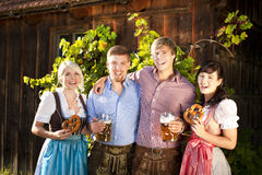 Four young people with beer glasses and bretzel Stock Photos