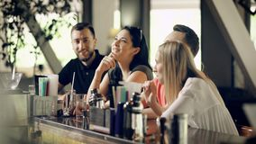 Four young people in casual clothes are talking and laughing sitting at bar counter in summer day. Two men and two women stock video