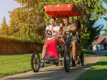 Four young people in a four-wheeled bicycle Royalty Free Stock Photography