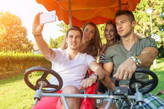 Four young people in a four-wheeled bicycle, they do selfie.  Stock Image