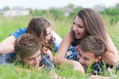 Four young people friends lying together on green grass outdoors Stock Image