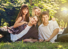 Four young people on the green lawn in park Royalty Free Stock Image