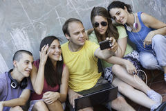 Four young people having fun. Outdoors with digital camera and laptop computer Stock Image