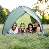 Four young people lying in a tent, looking at camera Stock Images