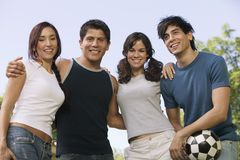 Four young people at park man holding soccer ball. Royalty Free Stock Image