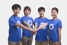 Four young people in recycling t-shirts with hands together, studio shot Stock Photo