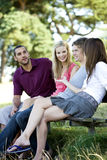 Four young people sitting on a bench, talking Stock Image