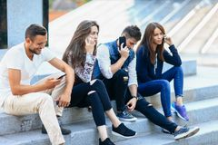 Four young people sitting on stairs and using mobile phones. Two women and one men talking on smartphone and one guy browsing. Modern life and technology Stock Photos