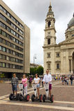 Four young people standing on a segway in front of the Budapest basilica Royalty Free Stock Image