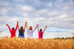 Four young people staying with raised hands royalty free stock photography