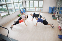 Four young people stretching and looking at the camera in an aerobics class Stock Images