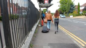 Four young people on summer vacation goes to the railway station with suitcase, guitar and backpack. stock video footage