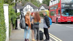 Four young people on summer vacation standing near the bus station with suitcase, guitar and backpack. stock video