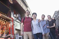 Four young people walking down street, near candied haw vendor. Stock Photography