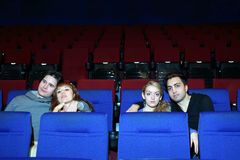 Four young people watch movie in cinema theater. Royalty Free Stock Photography