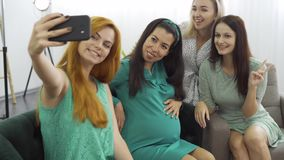 Four young pretty caucasian girls making group selfie. Smiling women taking photo with their pregnant friend. Cheerful. Female company celebrating pre-birth stock video