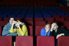 Four young scared friends see movie in cinema theater Stock Photos
