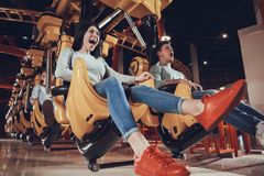 Four young scared friends sitting on carousel and screaming while riding at amusement park. Terrible emotions concept royalty free stock photography