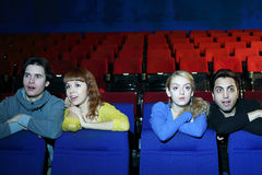 Four young scared and surprised people watch movie stock photography