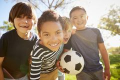 Four young schoolboys leaning in to camera holding football royalty free stock photos