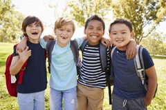 Four young smiling schoolboys hanging out on a school trip royalty free stock photography