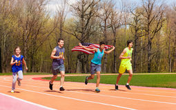 Four young sprinters waving American flag on track. Group of four running friends, teenage athletes, waving American flag in the stadium race athletics Stock Photo