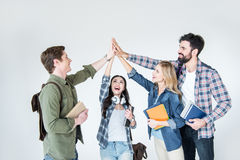 Four young students in casual clothes holding books and giving highfive. On white royalty free stock photo