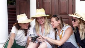 Four young stylish women in straw hats are sitting at the street. And watching the photos on the retro camera stock footage