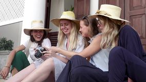 Four young stylish women in straw hats are sitting at the street. And watching the photos on the retro camera stock video