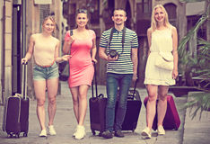 Four young traveling persons walking in city Royalty Free Stock Photos