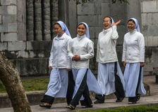Four young Vietnamese nuns in Ao Dai going to church service. Stock Image