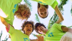 Four young volunteers in green t-shirts with a picture of recycle forming huddles under palm trees on the shore of an. Ocean beach, after cleaning the beach stock video footage