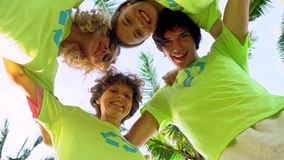 Four young volunteers in green t-shirts with a picture of recycle forming huddles under palm trees on the shore of an. Ocean beach, after cleaning the beach stock video
