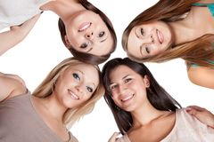 Four young woman looking down. Four attractive young women looking down at the camera with their heads close together isolated on white Royalty Free Stock Photography