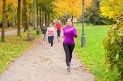 Four young woman out running together in a park Stock Photo