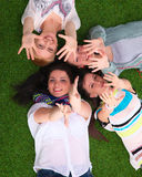 Four young women lying on green grass with hands Stock Photography