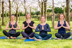 Four young women practicing Lotus Pose Royalty Free Stock Images