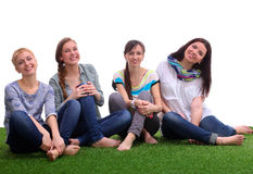 Four young women sitting  on green grass Stock Photography