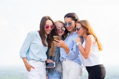 Four young women in sunglasses use smartphone standing on the roof of the building. Friendship and modern technology concepts stock photos