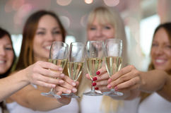 Four young women toasting with champagne. Four young women toasting with glasses of champagne to celebrate a happy event or see in the new year, close up focus Stock Photo