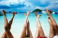 Four young women on a tropical beach. Stretching up slender legs Stock Photography