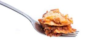 Fourchette avec le lasagne sur le blanc Photo libre de droits