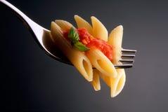 Fourchette avec les pâtes et le basilic de tomate photo libre de droits