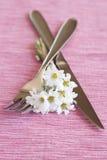 Fourchette, couteau et un petit bouquet des fleurs Photos stock