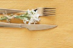 Fourchette, couteau et un petit bouquet des fleurs Photo stock