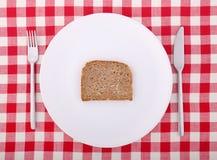 Fourchette, couteau et une part de pain d'une plaque photographie stock libre de droits