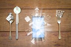 Fourchette, cuillère et couteau avec le smartphone et icônes d'application économique sur le fond en bois grunge de vintage Image libre de droits