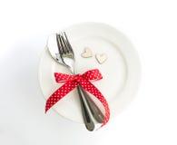 Fourchette d'arrangement de dîner d'amour et lien de cuillère avec le ruban rouge du plat Photos libres de droits